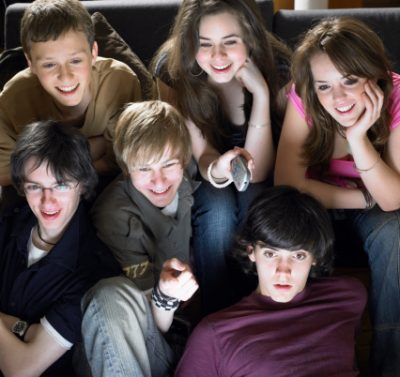 Group of teenagers (15-17) watching tv, smiling